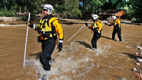 Members of the FEMA Urban Search and Rescue Nebraska Task Force 1 use probes to test for water depth while crossing floodwaters looking for missing people near Longmont, Colorado, on September 17. Stranded flood victims are being rescued by military helicopters and vehicles.