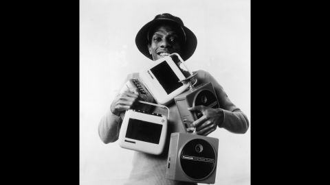 """The cassette was introduced in 1963; the 8-track tape in 1964. Both were portable ways of listening to music. Here, actor Jimmie Walker (as his """"Good Times"""" character J.J.) poses with several 8-track and cassette players."""