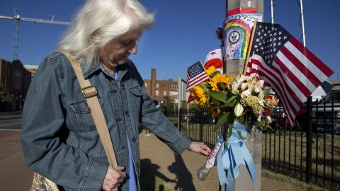 """A woman who said she works at the Washington Navy Yard looks at a memorial to the shooting victims on Wednesday, September 18. Authorities said 12 people -- plus the gunman -- were killed in the shooting on Monday, September 16. <a href=""""http://www.cnn.com/2013/09/16/us/gallery/navy-yard-shooting/index.html"""">View photos from the scene of the rampage.</a>"""