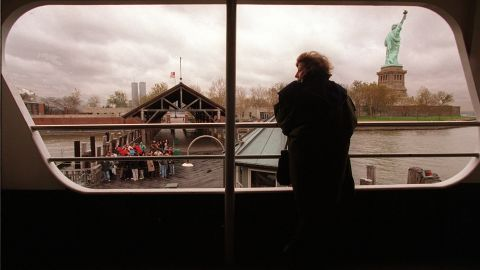 A tourist peers out a ferry window at the Statue of Liberty on November 14, 1995, as a small group of visitors wait on the dock to board the vessel. No passengers were allowed off the boat as both the Statue of Liberty and Ellis Island were closed after federal workers were sent home.