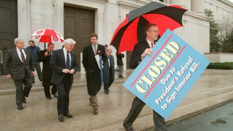 """House Appropriations Committee Chairman Rep. Bob Livingston, right, holds a """"closed"""" sign outside the National Gallery of Art in Washington on December 18, 1995."""