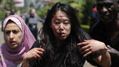 Elaine Dang of San Diego is helped to safety after the attack. The military asked local media not to televise anything live because the gunmen are watching the screens in the mall.