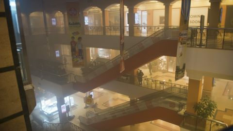 Armed police take cover behind escalators as smoke fills the air. Witnesses say tear gas was thrown in the corridors.