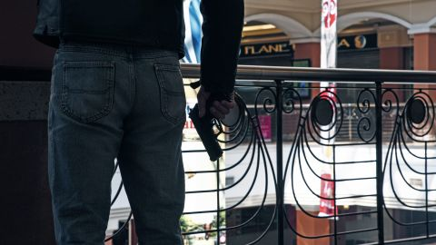 An armed official takes a shooting position inside the mall.