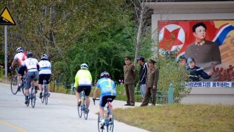 Riders passing a propaganda monument of Dear Leader Kim Jong-il.