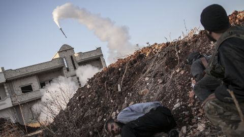 Free Syrian Army fighters take cover moments after firing a rocket toward government forces in the Idlib province of northern Syria on Friday, September 20.