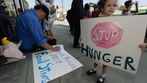 A girl  joins her father and other activists in June in Los Angeles protesting a farm bill that would cut funding for SNAP, or the food stamp program.