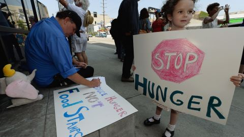 A girl joins her father and others in June in Los Angeles protesting a bill that would cut funding for SNAP, or food stamps.