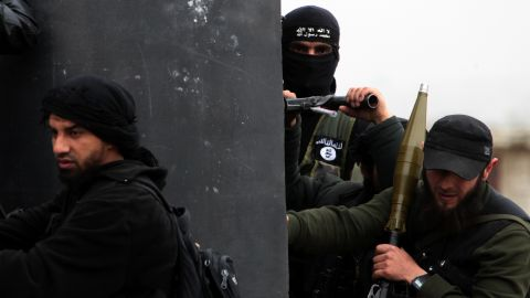 A Turkish fighter of the jihadist group Al-Nusra Front, bearing the flag of Al-Qaeda on his jacket (C-back), holds position with fellow comrades on April 4, 2013 in the Syrian village of Aziza, on the southern outskirts of Aleppo.