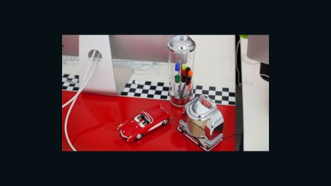 """Brit + Co. sponsored a """"Pimp My Desk"""" contest for its employees. Winner Dzuy Linh created a diner-themed desk using 1950s-themed objcts as accessories and vinyl decals to create a red and checkerboard base."""