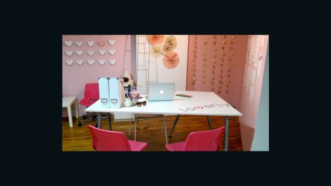 Lover.ly's office walls are decorated in a pink splash that matches the logo of the wedding inspiration site. The team also created paper heart-shaped art for wall decor.