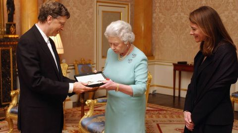 """Britain's Queen Elizabeth II presents Gates with an honorary knighthood, as his wife, Melinda Gates, watches. Despite the 2005 honor, Gates can't use the title """"Sir"""" because he's not a British citizen."""