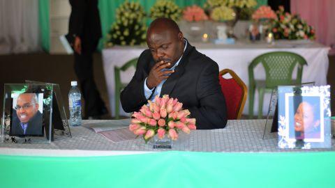 A man sits at a table with photos of Mbugua Mwangi and Mwangi's fiancee, Rosemary Wahito, during their funeral service in Nairobi on Friday, September 27. Mwangi was the nephew of Kenyan President Uhuru Kenyatta's.