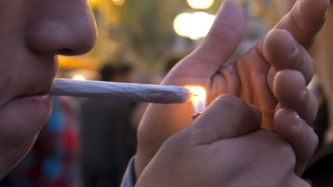 A young man lights a marijuana cigarette during a demonstration demanding a new law on cannabis in Montevideo on May 8, 2013. Lawmakers in Uruguay are studying a bill to legalize the cultivation of marijuana and allow limited personal consumption of it -- which if passed, will have authorities controlling its quality and the amount used. With the bill, which is supported by President Jose Mujica, the government wants to end drug-related violent crime which in recent years has emerged for the first time in the South American nation. AFP PHOTO/Pablo PORCIUNCULA (Photo credit should read PABLO PORCIUNCULA/AFP/Getty Images)