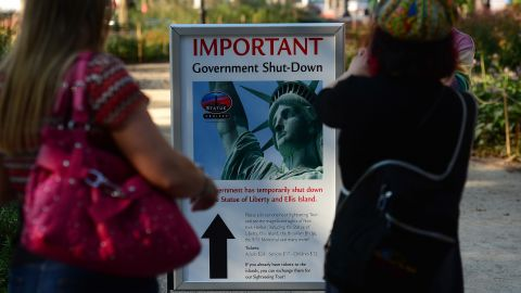 People look at a sign announcing that the Statue of Liberty is closed in New York on October 1.