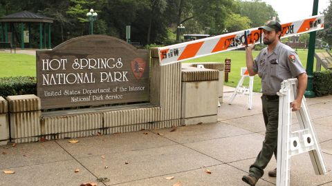 Hot Springs National Park employee Stacy Jackson carries a barricade while closing Arlington Lawn in Hot Springs National Park in Arkansas on October 1.