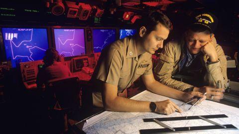 Tom Clancy, right, tours the U.S. battle cruiser Yorktown off the coast of Norfolk, Virginia in 1988.