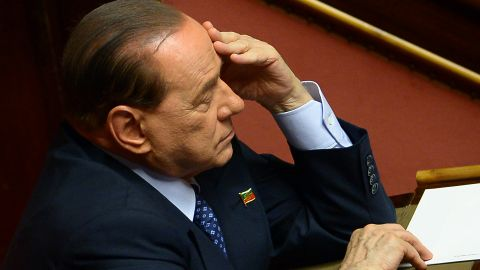 Former Prime Minister and leader of Forza Italia, Silvio Berlusconi listens to Italys' Prime Minister Enrico Letta during his speech on October 2, 2013 before today's confidence vote at the Parliament