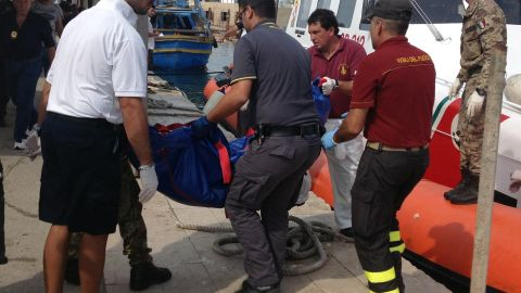 Firefighters unload the body of a drowned migrant from a coast guard boat in the port of Lampedusa on October 3.