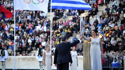 Actress Ino Menegaki (R), playing a high priestess, hands the Olympic flame to the president of the Hellenic Olympic Committee, Spyros Kapralos, on October 5, 2013 at the Panathenaic stadium in Athens during a handover ceremony of the Olympic flame for the the Sochi 2014 Olympic Winter Games which begin on February 7. AFP PHOTO / LOUISA GOULIAMAKI (Photo credit should read LOUISA GOULIAMAKI/AFP/Getty Images)