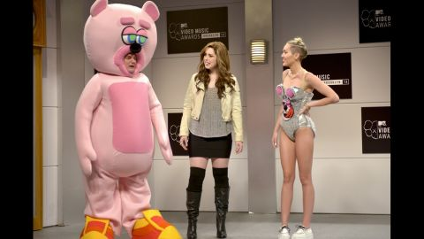 """Bobby Moynihan, left to right, Vanessa Bayer and Cyrus perform a skit on """"Saturday Night Live"""" on October 5, in which they mock Cyrus' VMA performance."""