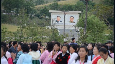 """Spectators waiting for the bikers to reach the finish line. In the background the """"Great"""" and """"Dear Leaders"""" Kim Il Sung and his son, Kim Jong-Il."""