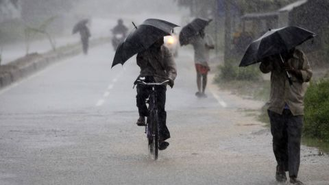 Villagers walking to the cyclone shelter try to block the heavy wind and rain with umbrellas near Chatrapur on October 12.