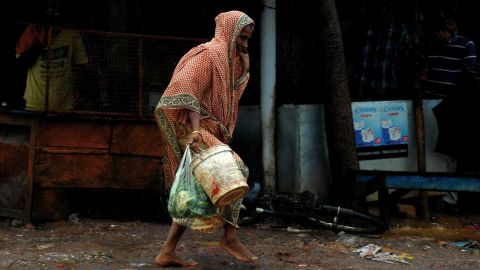 A woman carries daily essentials as she walks in a heavy wind in the town of Gopalpur on October 12.
