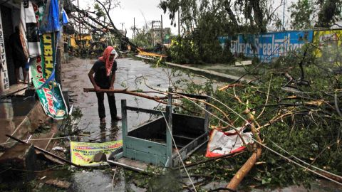 An man salvages a table stuck in uprooted trees fallen during the storm on a road in Berhampur on October 13.