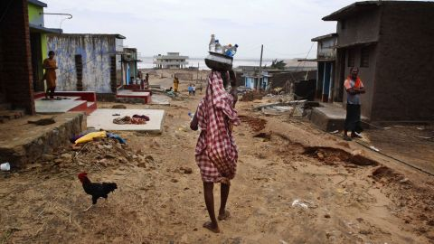 A villager carries drinking water in bottles as she arrives at the cyclone-hit village of Arjipalli on October 13.