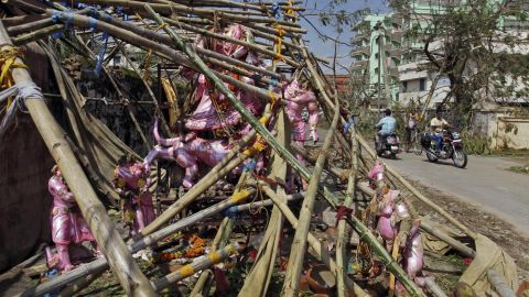 People drive past statues of Hindu gods and goddesses damaged during the storm in Berhampur, India, on October 14.