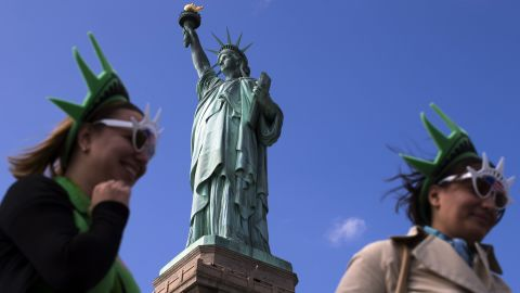 The Statue of Liberty looms over visitors below on Liberty Island in New York Harbor on Sunday, October 13, 2013. The statue was closed to the public by the federal government's partial shutdown that began October 1, 2013, but reopened Sunday after the state of New York agreed to shoulder the costs of running the site during the shutdown.
