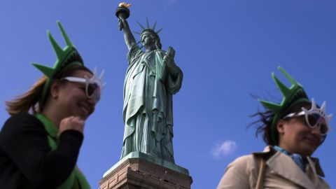 The Statue of Liberty looms over visitors below on Liberty Island in New York Harbor, on Sunday, October 13. The Statue of Liberty reopened to the public after the state of New York agreed to shoulder the costs of running the site during the partial federal government shutdown.