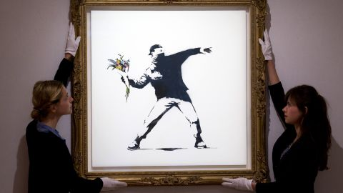 """Gallery assistants adjust Banksy's """"Love Is in the Air"""" ahead of an auction in London in June 2013. The piece was sold for $248,776."""
