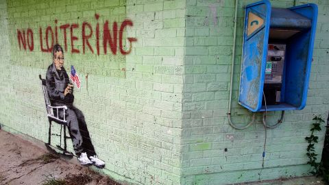"""Graffiti on the side of a building in New Orleans shows an elderly person in a rocking chair under the banner, """"No Loitering,"""" in 2008."""