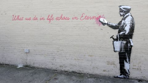 """A Banksy mural is seen on a wall in Queens. The quote is from the movie """"Gladiator."""" It says, """"What we do in life echoes in eternity."""""""