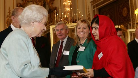 Malala gives a copy of her book to Britain's Queen Elizabeth II during a reception at Buckingham Palace in October 2013.