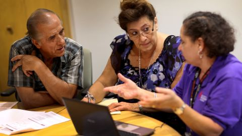 Affordable Care Act navigator Nini Hadwen (R) speaks with Jorge Hernandez (L) and Marta Aguirre as they shop for health insurance during a navigation session put on by the Epilepsy Foundation Florida to help people sign up for health insurance under the Affordable Care Act on October 8, 2013 in Miami, Florida. The United States government continues to be partially shut down as Republicans hold out hope to cut funding for the Affordable Care Act.