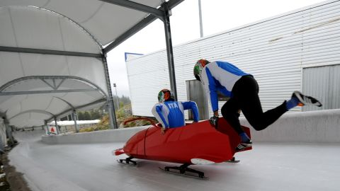 Bertazzo slides into the cockpit of his sled while his teammate sprints to power it from the start line.