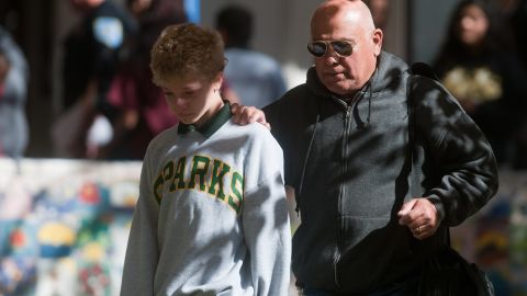 SPARKS, NV - OCTOBER 21:  A parent escorts his child from Agnes Risley Elementary school following a shooting at nearby Sparks Middle School October 21, 2013 in Sparks, Nevada. A staff member was killed and two students were injured after a student opened fire at the Nevada middle school. The suspected gunman was also killed. Students from the middle school were evacuated and held for parents at the elementary school.  (Photo by David Calvert/Getty Images)