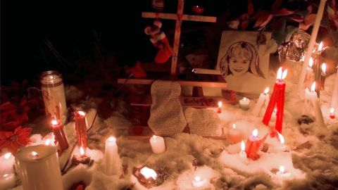 """Candles surround a portrait of JonBenet outside her Boulder home after a candlelight vigil on the one-year anniversary of her murder on December 26, 1997. A year after the murder, Boulder police indicated John and Patsy Ramsey were under """"an umbrella of suspicion,"""" and would  be questioned again."""