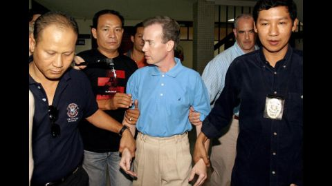 Thai police officials escort U.S. teacher John Mark Karr at the Thai Immigration Department in Bangkok on August 17, 2006. Officials announced Karr as a suspect in the case. Karr said he was present when JonBenet died, and that he loved her and her death was an accident. On August 26, 2006, the Boulder County District Attorney decided not to charge Karr in connection with the murder after DNA tests confirmed that he wasn't a match to the evidence found at the crime scene.