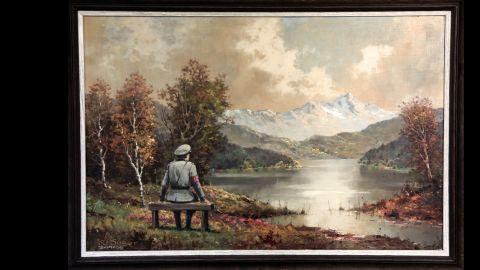"""""""The Banality of the Banality of Evil"""" actually started out as a thrift store painting in New York City. Once altered by Banksy, who inserted an image of a Nazi officer sitting on a bench, it was re-donated to the store in October 2013, according to the<a href=""""http://www.banksyny.com/"""" target=""""_blank"""" target=""""_blank""""> artist's site</a>."""