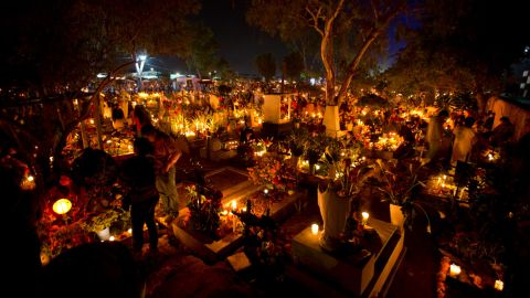 """""""Some choose to go to the grave site of the loved one instead of building an altar,"""" says Mexican-American writer Kathy Cano-Murillo,  owner of Crafty Chica in Phoenix, Arizona. """"Family and friends bring candles which are turned off to symbolize the end of their journey to our world."""""""