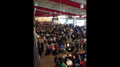 People wait in a terminal after flights were grounded because of the incident.