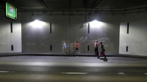 A family walks through a tunnel as they leave the airport.
