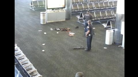 """This photo, from Terminal 3, shows what appears to be a weapon on the ground. Police said a man """"pulled an assault rifle out of a bag and began to open fire"""" Friday, killing one person and injuring others before being shot and taken into custody."""