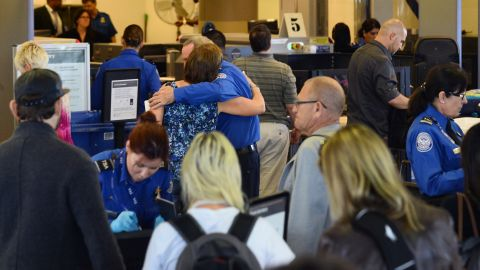 A passenger embraces a TSA screener at Los Angeles International Airport's Terminal 3 after it was reopened on Saturday, November 2 following a shooting.  Four other people are recovering from injuries in the shooting.