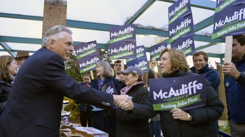 McAuliffe shakes hands with supporters after voting.