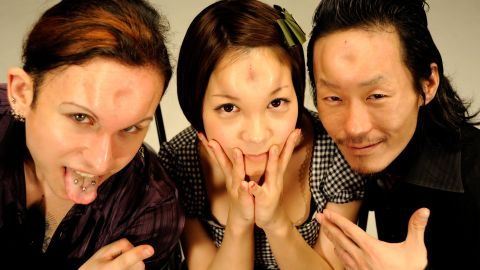 """John (left), Marin (center) and Scorpion (right) pose with their """"bagel heads"""" in Tokyo."""